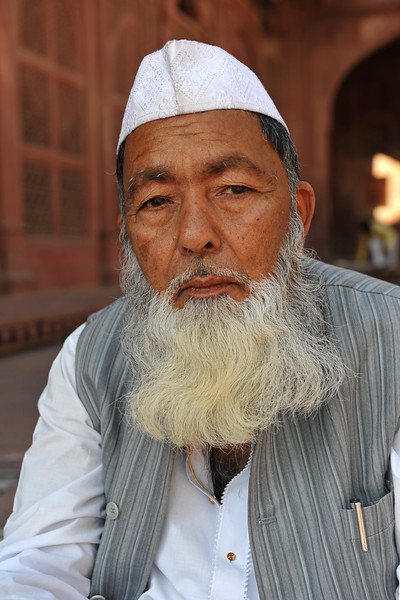 Old man near the tombs at Fatehpur Sikri.<br /> Fatehpur Sikri (Hindi: फतेहपुर सीकरी, Urdu: فتحپور سیکری) is a city and a municipal board in Agra district in the state of Uttar Pradesh, in North India. The historical city was constructed by Mughal Emperor Akbar beginning in 1570 and served as the empire's capital from 1571 until 1585. Though it took 15 years to build, it was abandoned after only 14 years of use because of shortage of water supply which was unable to sustain the growing population. The palace and mosque in Fatehpur Sikri are a tourist attraction and it is an UNESCO World Heritage Site which is about 40 km from the Taj Mahal, Agra. Uttar Pradesh state (UP), North India.