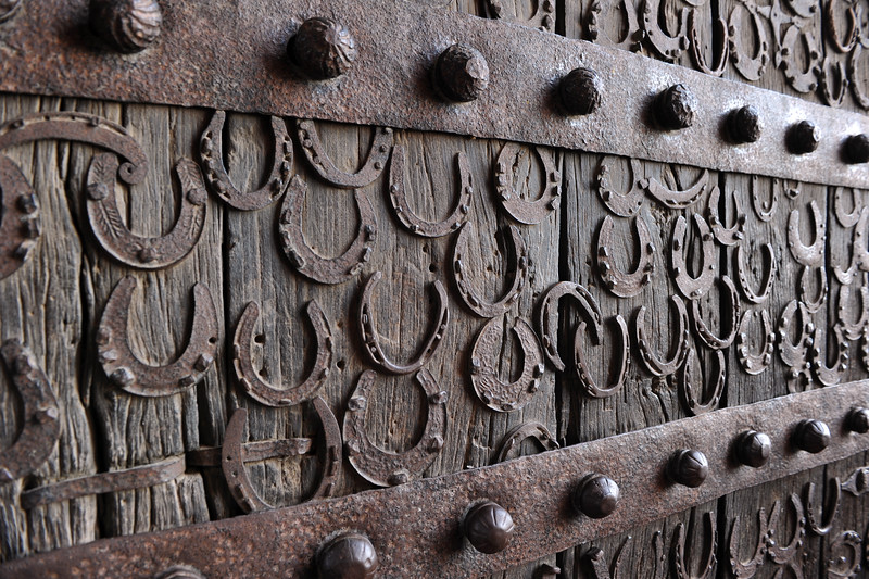 Horse shoes on the huge wooden door entrance to Fatehpur Sikri. <br /> Fatehpur Sikri (Hindi: फतेहपुर सीकरी, Urdu: فتحپور سیکری) is a city and a municipal board in Agra district in the state of Uttar Pradesh, in North India. The historical city was constructed by Mughal Emperor Akbar beginning in 1570 and served as the empire's capital from 1571 until 1585. Though it took 15 years to build, it was abandoned after only 14 years of use because of shortage of water supply which was unable to sustain the growing population. The palace and mosque in Fatehpur Sikri are a tourist attraction and it is an UNESCO World Heritage Site which is about 40 km from the Taj Mahal, Agra. Uttar Pradesh state (UP), North India.