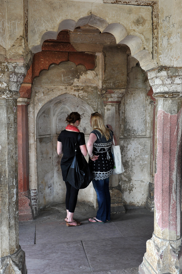 Visitors reading some of the stupid scribbling messages whch cause permanent damage to the walls. <br /> Inside of Agra Fort (Lal Qila) which is a UNESCO World Heritage site. It is about 2.5 km northwest of the Taj Mahal. The fort can be more accurately described as a walled palatial city.