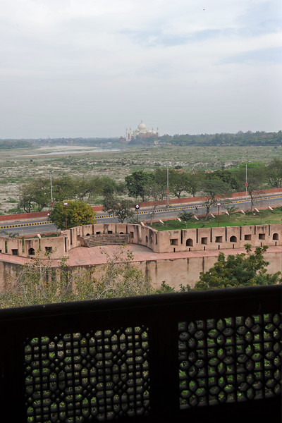 Agra Fort (Lal Qila) is a UNESCO World Heritage site. It is about 2.5 km northwest of the Taj Mahal. The fort can be more accurately described as a walled palatial city. Taj Mahal as seen from Agra Fort. At the end of his life, Shah Jahan who built Taj Mahal was imprisoned by his son, Aurangzeb, in the fort. It is rumored that Shah Jahan died in Muasamman Burj, a tower with a marble balcony with an excellent view of the Taj Mahal.