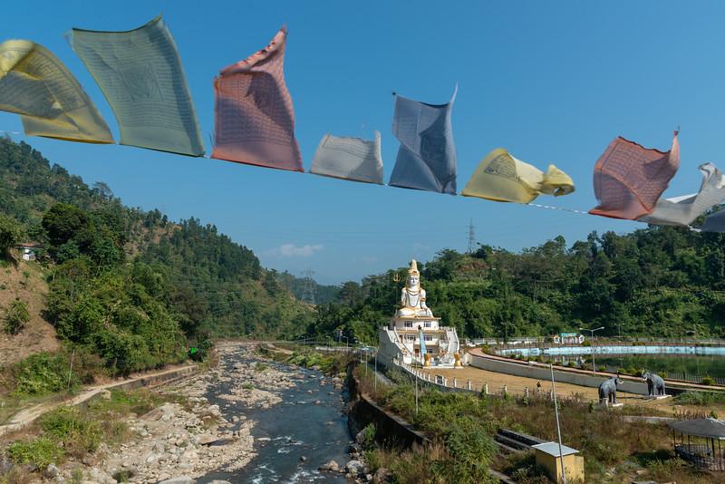 Prayer flags flying in the wind. Shiva Statue, शिव प्रतिमा, Shree Dwarika Estate, Publbazar-Jorethang Road, West Bengal, North East India.