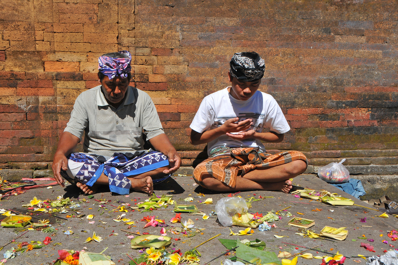 Praying at Tirta Empul - The Holy Springs<br /> <br /> Located in Tampak Siring is the Temple Tirta Empul where its pond is believed to cure sickness. Tirta empul means water that comes from the earth naturally. And until this day Balinese still believe the miraculous healing powers of the water and therefore bath in it. According to Usana Bali, an ancient Balinese manuscript, there was once an evil king named Maya Denawa who did not believe in god, and objected to the people worshipping gods. The gods sent a punishment in the form of the warriors of Bhatara Indra, who arrived to attack Maya Denawa and overthrow him. However, Maya Denawa poisoned the warriors and they lay dead. Seeing this, the Hindu God Indra pierced the earth to create a spring called Amerta. When the water was sprinkled over the dead warriors, they became alive again. This water source is believed to be Tirta Empul - the source of life and prosperity to this day. The temple inscriptions mention that Tirta Empul was constructed in 960 AD, when the king Chandrabhaya Singha Warmadewa ordered its construction. During a festival or ceremony you can see many people bathing in the ponds that has seven pancuran. It is believed that the sacred spring water not only can cure sickness but can also purify sins.