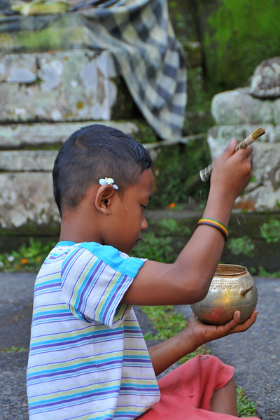 Children at Goa Gajah perform a Hindu ritual ceremony. <br /> Elephant Cave, is located on the island of Bali near Ubud and a short distance from Bedulu. Built in the 9th century, it served as a sanctuary. A carved entrance depicts entangling leaves, rocks, animals, ocean waves and demonic human shapes running from the gaping mouth which forms the entrance to the cave. The facade of the cave is a relief of various menacing creatures and demons carved right into the rock at the cave entrance. The primary figure was once thought to be an elephant, hence the nickname Elephant Cave. The site is mentioned in the Javanese poem Desawarnana written in 1365. Inside the cave one finds the Shiva lingum.<br /> <br /> The monstrous Kala head that looms above the entrance seems to part the rock with her hands. Similarly decorated hermit cells are also found in Java. The large earrings indicate that the figure is that of a woman. The T-shaped interior of the rock-hewn cave contained niches which probably served as compartments for ascetics.<br /> <br /> Goa Gajah is named after Sungai Petanu (Elephant River not an elephant as elephants are not found in Bali) and dates back to the 11th Century where it originally served as a dwelling for Hindu priests. Outside the cave at the pavilion is a statue of Men Brayut, the Balinese woman who together with her husband Pan could not stop having kids. The legend of Men Brayut is also represented in local Buddhist writings, under the name of Hariti, indicating a possible Buddhist association with Goa Gajah as well as Hindu.  Outside the cave, an extensive bathing place on the site was not excavated until the 1950s. These appear to have been built to ward off evil spirits. It is an UNESCO World Heritage site.