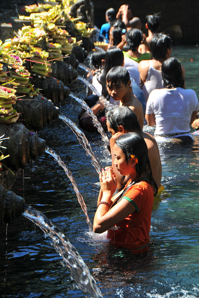 Tirta Empul - The Holy Springs<br /> <br /> Located in Tampak Siring is the Temple Tirta Empul where its pond is believed to cure sickness. Tirta empul means water that comes from the earth naturally. And until this day Balinese still believe the miraculous healing powers of the water and therefore bath in it. According to Usana Bali, an ancient Balinese manuscript, there was once an evil king named Maya Denawa who did not believe in god, and objected to the people worshipping gods. The gods sent a punishment in the form of the warriors of Bhatara Indra, who arrived to attack Maya Denawa and overthrow him. However, Maya Denawa poisoned the warriors and they lay dead. Seeing this, the Hindu God Indra pierced the earth to create a spring called Amerta. When the water was sprinkled over the dead warriors, they became alive again. This water source is believed to be Tirta Empul - the source of life and prosperity to this day. The temple inscriptions mention that Tirta Empul was constructed in 960 AD, when the king Chandrabhaya Singha Warmadewa ordered its construction. During a festival or ceremony you can see many people bathing in the ponds that has seven pancuran. It is believed that the sacred spring water not only can cure sickness but can also purify sins.