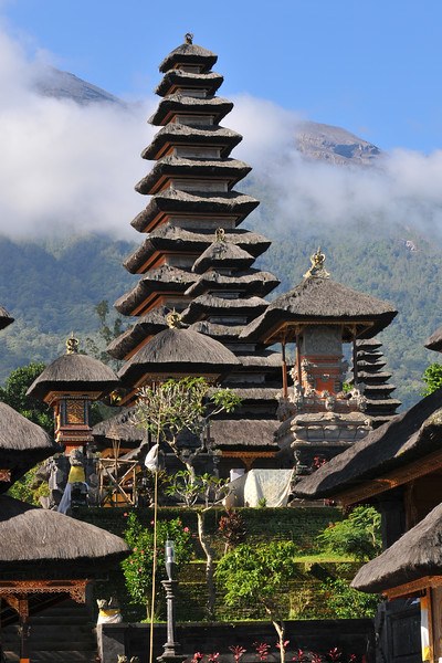 "Low lying clouds drift past the mountain and behind the temple.<br /> The Mother Temple of Besakih - Pura Besakih in the village of Besakih on the slopes of Mount Agung in eastern Bali, is the most important temple of Agama Hindu Dharma in Bali, Indonesia and is one of a series of Balinese temples. It has been nominated as an UNESCO World Heritage Site.<br /> <br /> A series of eruptions of Mount Agung in 1963, which killed approximately 1,700 people also threatened Puru Besakih but fortunately, the lava flows missed the temple complex by mere yards. The saving of the temple is regarded by the Balinese people as miraculous, and a signal from the Gods.<br /> <br /> This temple was built in a holy village named Hulundang Basukih, which is known today as Besakih village. The name of Besakih was derived from the word ""Basuki"" or in some old manuscripts written as Basukir or Basukih. The word Basuki itself was taken from the word ""Wasuki"" on the Sunskrit, which means ""salvation"".<br /> <br /> The mythology of Samudramanthana mentioned that Basuki was the name of a dragon that coiled around the Mandara Mountain.<br /> <br /> The old remains say that the Besakih Temple was built by Rsi Markandya and his followers in the 11th century. At that time, Rsi Markandya intended to go to Mount Agung to build a residence. The construction was troubled by a disease which caused the death of his followers. For the safety of them, he constructed a veneration to worship God for a salvation. The veneration was called ""Sanggar Basuki""."