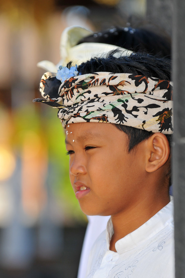 "Young boys at the The Mother Temple of Besakih.<br /> The Mother Temple of Besakih - Pura Besakih in the village of Besakih on the slopes of Mount Agung in eastern Bali, is the most important temple of Agama Hindu Dharma in Bali, Indonesia and is one of a series of Balinese temples. It has been nominated as an UNESCO World Heritage Site.<br /> <br /> A series of eruptions of Mount Agung in 1963, which killed approximately 1,700 people also threatened Puru Besakih but fortunately, the lava flows missed the temple complex by mere yards. The saving of the temple is regarded by the Balinese people as miraculous, and a signal from the Gods.<br /> <br /> This temple was built in a holy village named Hulundang Basukih, which is known today as Besakih village. The name of Besakih was derived from the word ""Basuki"" or in some old manuscripts written as Basukir or Basukih. The word Basuki itself was taken from the word ""Wasuki"" on the Sunskrit, which means ""salvation"".<br /> <br /> The mythology of Samudramanthana mentioned that Basuki was the name of a dragon that coiled around the Mandara Mountain.<br /> <br /> The old remains say that the Besakih Temple was built by Rsi Markandya and his followers in the 11th century. At that time, Rsi Markandya intended to go to Mount Agung to build a residence. The construction was troubled by a disease which caused the death of his followers. For the safety of them, he constructed a veneration to worship God for a salvation. The veneration was called ""Sanggar Basuki""."