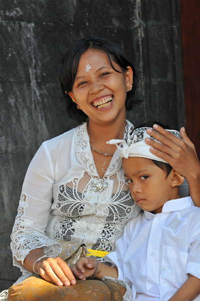 """Mother and son at The Mother Temple of Besakih after the worship.<br /> The Mother Temple of Besakih - Pura Besakih in the village of Besakih on the slopes of Mount Agung in eastern Bali, is the most important temple of Agama Hindu Dharma in Bali, Indonesia and is one of a series of Balinese temples. It has been nominated as an UNESCO World Heritage Site.<br /> <br /> A series of eruptions of Mount Agung in 1963, which killed approximately 1,700 people also threatened Puru Besakih but fortunately, the lava flows missed the temple complex by mere yards. The saving of the temple is regarded by the Balinese people as miraculous, and a signal from the Gods.<br /> <br /> This temple was built in a holy village named Hulundang Basukih, which is known today as Besakih village. The name of Besakih was derived from the word """"Basuki"""" or in some old manuscripts written as Basukir or Basukih. The word Basuki itself was taken from the word """"Wasuki"""" on the Sunskrit, which means """"salvation"""".<br /> <br /> The mythology of Samudramanthana mentioned that Basuki was the name of a dragon that coiled around the Mandara Mountain.<br /> <br /> The old remains say that the Besakih Temple was built by Rsi Markandya and his followers in the 11th century. At that time, Rsi Markandya intended to go to Mount Agung to build a residence. The construction was troubled by a disease which caused the death of his followers. For the safety of them, he constructed a veneration to worship God for a salvation. The veneration was called """"Sanggar Basuki""""."""
