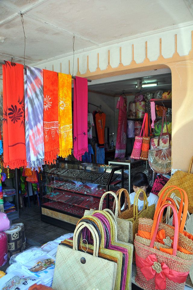"Bags and dress material on sale in Sukawati.<br /> In Central-East of Bali is Sukawati. In the the centre of town is the renowned Pasar Seni, undoubtedly the best place to shop in Bali. The two-storey market is a maze of alleyways with a massive array of artefacts, paintings, fabrics, clothing and basketware all crammed together so tight it is sometimes difficult to weave your way through it all. Other goods for sale include Sarongs, light blankets, lengths of Ikat cloth and practically all ceremonial paraphernalia.<br /> <br /> Sukawati has a traditional market on the main road of Bali with some side streets as well. It has a nice art market as well as a number of items such as large variety of woven baskets, Balinese ceremonial items made from colourful ""Prada"" (gold painted cloth), paintings, all types of handicrafts and fabrics. Be prepared for major bargaining to get a really good price. Bali, Indonesia."