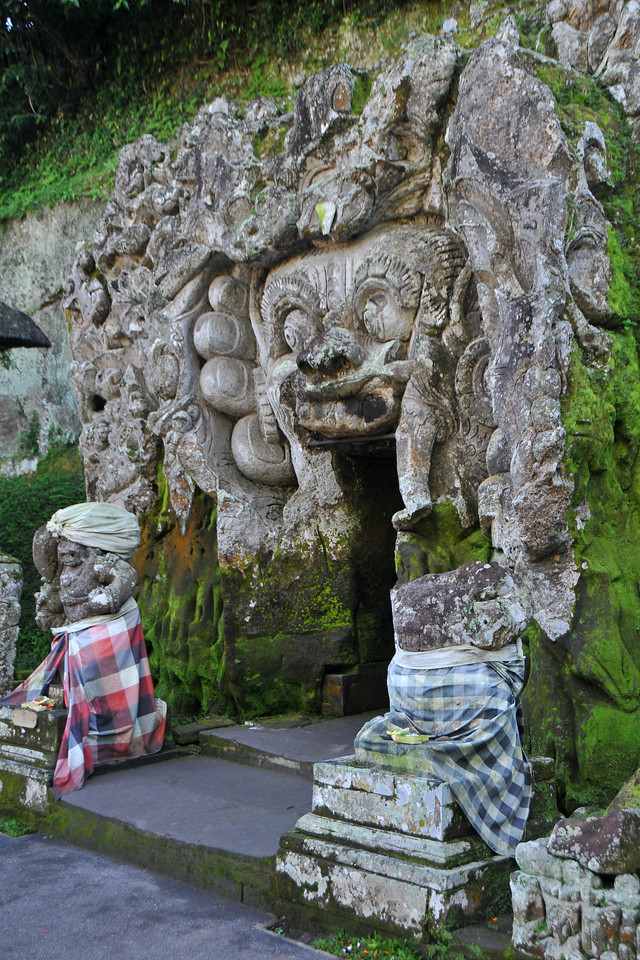Goa Gajah, or Elephant Cave, is located on the island of Bali near Ubud and a short distance from Bedulu. Built in the 9th century, it served as a sanctuary. A carved entrance depicts entangling leaves, rocks, animals, ocean waves and demonic human shapes running from the gaping mouth which forms the entrance to the cave. The facade of the cave is a relief of various menacing creatures and demons carved right into the rock at the cave entrance. The primary figure was once thought to be an elephant, hence the nickname Elephant Cave. The site is mentioned in the Javanese poem Desawarnana written in 1365. Inside the cave one finds the Shiva lingum.<br /> <br /> The monstrous Kala head that looms above the entrance seems to part the rock with her hands. Similarly decorated hermit cells are also found in Java. The large earrings indicate that the figure is that of a woman. The T-shaped interior of the rock-hewn cave contained niches which probably served as compartments for ascetics.<br /> <br /> Goa Gajah is named after Sungai Petanu (Elephant River not an elephant as elephants are not found in Bali) and dates back to the 11th Century where it originally served as a dwelling for Hindu priests. Outside the cave at the pavilion is a statue of Men Brayut, the Balinese woman who together with her husband Pan could not stop having kids. The legend of Men Brayut is also represented in local Buddhist writings, under the name of Hariti, indicating a possible Buddhist association with Goa Gajah as well as Hindu.  Outside the cave, an extensive bathing place on the site was not excavated until the 1950s. These appear to have been built to ward off evil spirits. It is an UNESCO World Heritage site.