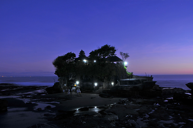 """Sunset at Tanah Lot.<br /> Tanah Lot is a a popular motif for tourists taking pictures of Bali. Its an iconic structure. Photographing the rock formation off the Indonesian island of Bali is on every tourists list. Tanah Lot is the home of a pilgrimage temple, the Pura Tanah Lot and literally means """"Land in the Middle of the sea"""" in Balinese language. Located in Tabanan, about 20 km from Denpasar, the temple sits on a large offshore rock which has been shaped continuously over the years by the ocean tide striking it.<br /> <br /> It is claimed that Tanah Lot is the work & result of the efforts of the 15th century priest Nirartha. During his travels along the south coast he saw the rock-island's beautiful setting and rested there. Some fishermen saw him, and bought him gifts. Nirartha then spent the night on the little island. Later he spoke to the fishermen and told them to build a shrine on the rock for he felt it to be a holy place to worship the Balinese sea Gods. The Tanah Lot temple was built and has been a part of Balinese mythology for centuries. The temple is one of seven sea temples around the Balinese coast. Each of the sea temples were established within eyesight of the <br /> next to form a chain along the south-western coast.<br /> <br /> At the base of the rocky island, poisonous sea snakes are believed to guard the temple from evil spirits and <br /> intruders. As well as one giant snake which also protects the temple, which was created from Nirartha's scarf <br /> when he established the island. In 1980 the temple's rock face was starting to crumble and the area around and inside the temple started to become dangerous. The Japanese government then provided a loan to the Indonesia government of Rp. 800 Billion to restore & conserve the historic temple and other beach locations around the island of Bali. As a result, over one third of the rock which can be seen is artificial created under the Japanese upgrade works. On the down side, the area leading t"""