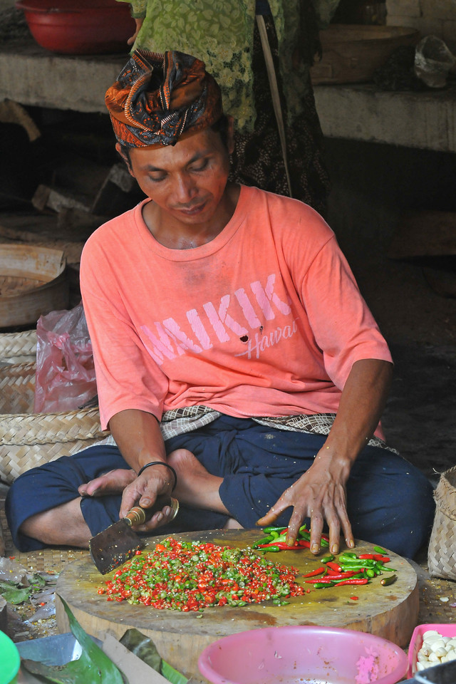Chopping red & green chillies.<br /> Food being cooked at the Dalem Agung Padantegal Temple, Sacred Monkey Forest, Ubud for the ceremonial feeding.<br /> <br /> Bali is an Indonesian island with the provincial capital at Denpasar. Lying between Java to the west and Lombok to the east, the island is home to the largest tourist destination in the country and is renowned for its highly developed arts, including dance, sculpture, painting, leather, metalworking and music. What's interesting is that while Indonesia has the world's largest Muslim population, on the island of Bali, 93% of the population is Balinese Hindu and one can find Hinduism in each and every aspect of the life and living.