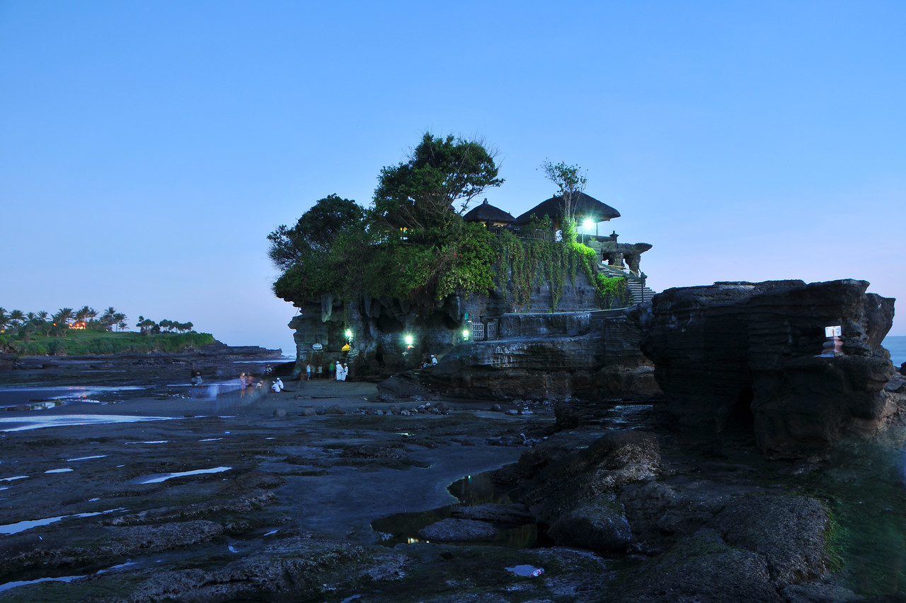 "Sunset at Tanah Lot.<br /> Tanah Lot is a a popular motif for tourists taking pictures of Bali. Its an iconic structure. Photographing the rock formation off the Indonesian island of Bali is on every tourists list. Tanah Lot is the home of a pilgrimage temple, the Pura Tanah Lot and literally means ""Land in the Middle of the sea"" in Balinese language. Located in Tabanan, about 20 km from Denpasar, the temple sits on a large offshore rock which has been shaped continuously over the years by the ocean tide striking it.<br /> <br /> It is claimed that Tanah Lot is the work & result of the efforts of the 15th century priest Nirartha. During his travels along the south coast he saw the rock-island's beautiful setting and rested there. Some fishermen saw him, and bought him gifts. Nirartha then spent the night on the little island. Later he spoke to the fishermen and told them to build a shrine on the rock for he felt it to be a holy place to worship the Balinese sea Gods. The Tanah Lot temple was built and has been a part of Balinese mythology for centuries. The temple is one of seven sea temples around the Balinese coast. Each of the sea temples were established within eyesight of the <br /> next to form a chain along the south-western coast.<br /> <br /> At the base of the rocky island, poisonous sea snakes are believed to guard the temple from evil spirits and <br /> intruders. As well as one giant snake which also protects the temple, which was created from Nirartha's scarf <br /> when he established the island. In 1980 the temple's rock face was starting to crumble and the area around and inside the temple started to become dangerous. The Japanese government then provided a loan to the Indonesia government of Rp. 800 Billion to restore & conserve the historic temple and other beach locations around the island of Bali. As a result, over one third of the rock which can be seen is artificial created under the Japanese upgrade works. On the down side, the area leading to Tanah Lot is highly commercialised and visito"