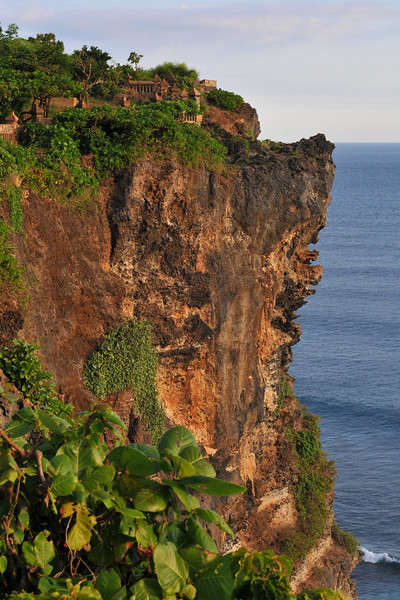Steep cliff and shoreline visible at Pura Luhur Uluwatu, Bali. <br /> Pura Luhur Uluwatu is one of Bali's kayangan jagat (directional temples) and guards Bali from evil spirits from the south-west. Major Hindu deities dwell in Uluwatu such as - Bhatara Rudra, God of the elements and of cosmic force majeures. Bali's most spectacular temples located high on a cliff top at the edge of a plateau 250 feet above the waves of the Indian Ocean. Uluwatu lies at the southern tip of Bali in Badung Regency. Dedicated to the spirits of the sea, the famous Pura Luhur Uluwatu temple is an architectural wonder in black coral rock, beautifully designed with spectacular views. This is a popular place to enjoy the sunset. Famous not only for its unique position, Uluwatu also boasts one of the oldest temples in Bali, Pura Uluwatu. Most of Bali's regencies have Pura Luhur (literally high temples or ascension temples) which become the focus for massive pilgrimages during three or five day odalan anniversaries. The photogenic Tanah Lot and the Bat Cave temple, Goa Lawah, are also Pura Luhur. Not all Pura Luhur are on the coast, however but all have inspiring locations, overlooking large bodies of water.<br /> <br /> Uluwatu is a small village on the west coast, south of Jimbaran, but for most visitors it refers only to the famous temple of the same name and several kilometers further south at the coast. A taxi from Kuta to Uluwatu takes about 30 minutes up and down winding roads.<br /> <br /> The temple is inhabited by large number of monkeys, who are extremely adept at snatching visitors' belonging, including bags, cameras and eyeglasses. One has to keep a very close grip on all your belongings. Anu carried a stick like some others and I carried my tripod. :)<br /> If you do have something taken, the monkeys can usually be induced to exchange it for some fruit. Needless to say, rewarding the monkeys like this only encourages them to steal more. Locals and even the temple priests will be happy to do the job for you, natural