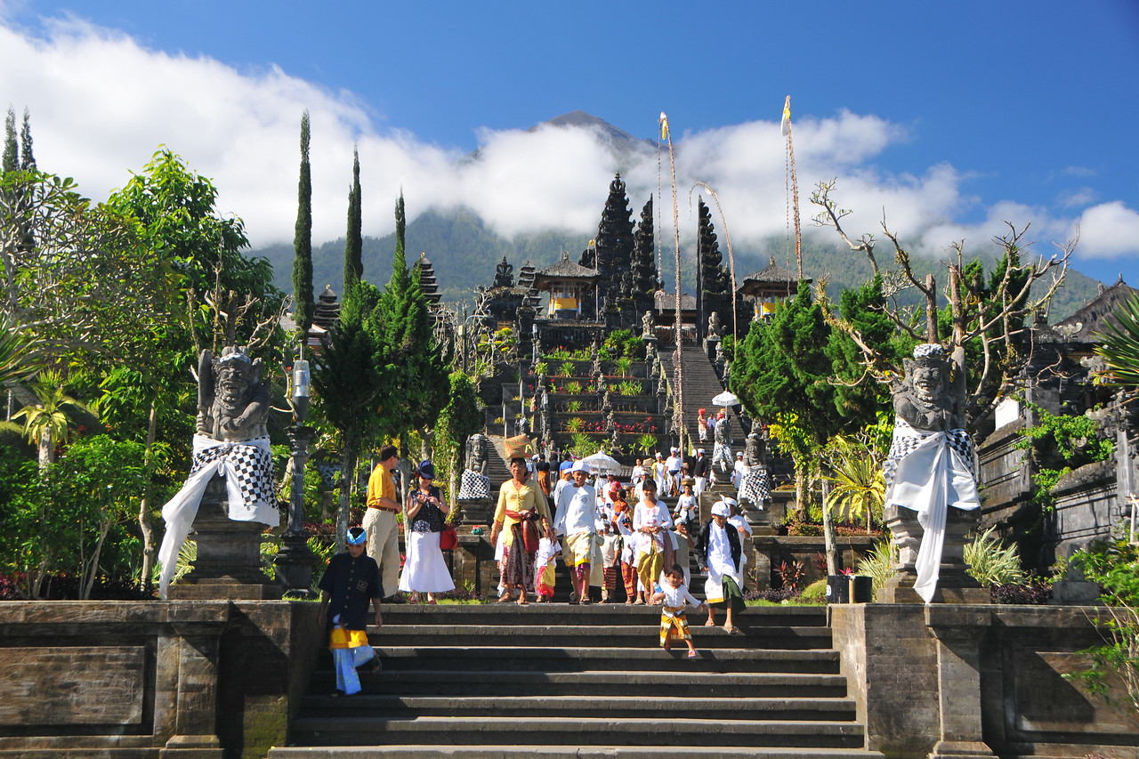 "As we reached The Mother Temple of Besakih, we saw a group of Balinese returning from the temple. When someone dies in the family after sometime the whole family goes to the temple and prays for the departed soul.<br /> <br /> The Mother Temple of Besakih - Pura Besakih in the village of Besakih on the slopes of Mount Agung in eastern Bali, is the most important temple of Agama Hindu Dharma in Bali, Indonesia and is one of a series of Balinese temples. It has been nominated as an UNESCO World Heritage Site.<br /> <br /> A series of eruptions of Mount Agung in 1963, which killed approximately 1,700 people also threatened Puru Besakih but fortunately, the lava flows missed the temple complex by mere yards. The saving of the temple is regarded by the Balinese people as miraculous, and a signal from the Gods.<br /> <br /> This temple was built in a holy village named Hulundang Basukih, which is known today as Besakih village. The name of Besakih was derived from the word ""Basuki"" or in some old manuscripts written as Basukir or Basukih. The word Basuki itself was taken from the word ""Wasuki"" on the Sunskrit, which means ""salvation"".<br /> <br /> The mythology of Samudramanthana mentioned that Basuki was the name of a dragon that coiled around the Mandara Mountain.<br /> <br /> The old remains say that the Besakih Temple was built by Rsi Markandya and his followers in the 11th century. At that time, Rsi Markandya intended to go to Mount Agung to build a residence. The construction was troubled by a disease which caused the death of his followers. For the safety of them, he constructed a veneration to worship God for a salvation. The veneration was called ""Sanggar Basuki""."
