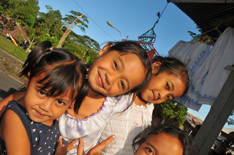 Children playing pranks and striking a pose near The Mother Temple of Besakih - Pura Besakih in the village of Besakih on the slopes of Mount Agung in north-eastern Bali, is the most important temple of Agama Hindu Dharma in Bali, Indonesia and is one of a series of Balinese temples.