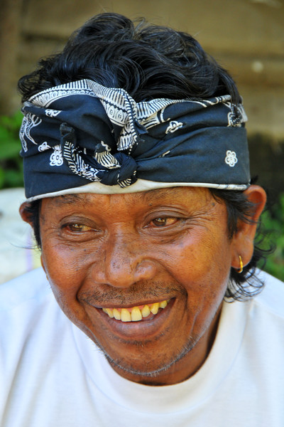 """Close up portrait of the food vendor at the BALI ART CENTER<br /> <br /> It is located on Nusa Indah Street, about 2 Kms distance from the City Centre or Puputan Badung Park. The Art Centre was officially opened in February 14th, 1973. The Art Centre is a building - complex with Balinese traditional architecture with an extent of about 5 hectares consisted of: Exhibition Hall called Mahudara Mandhara Giri Bhuana where paintings and other traditional Balinese objects are exhibited. The Hall is located on the north side of the Art Centre Complex. The Ksirarnawa Hall, a two-storey hall in which various kinds of performing arts are on stage on the upper floor white exhibitions of handicrafts, gold and silverworks are held on the first floor. The Ardha Candra open stage is located on the Eastern side, on which traditional performing-arts, music-concerts and fashion-shows are often held, The Wantilan Hall is also used for similar purpose. The Art Centre had the Arts festival going on when we visited. <br /> See more details at:  <a href=""""http://www.baliartsfestival.com/"""">http://www.baliartsfestival.com/</a>"""