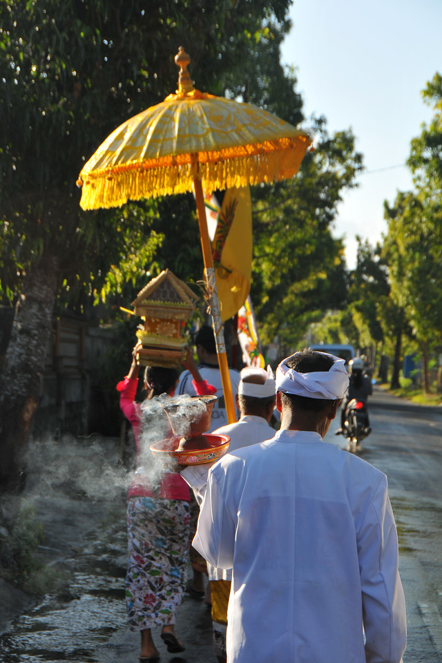 Women and men dressed traditionally carry offerings. Enroute from Denpasar International Airport to Ubud, we see a Hindu procession.<br /> <br /> Bali is an Indonesian island with the provincial capital at Denpasar. Lying between Java to the west and Lombok to the east, the island is home to the largest tourist destination in the country and is renowned for its highly developed arts, including dance, sculpture, painting, leather, metalworking and music. What's interesting is that while Indonesia has the world's largest Muslim population, on the island of Bali, 93% of the population is Balinese Hindu and one can find Hinduism in each and every aspect of the life and living.