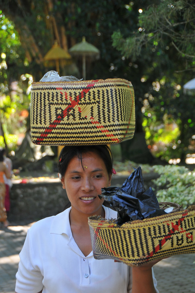 Lady carrying offerings in her basket at Tirta Empul - The Holy Springs<br /> <br /> Located in Tampak Siring is the Temple Tirta Empul where its pond is believed to cure sickness. Tirta empul means water that comes from the earth naturally. And until this day Balinese still believe the miraculous healing powers of the water and therefore bath in it. According to Usana Bali, an ancient Balinese manuscript, there was once an evil king named Maya Denawa who did not believe in god, and objected to the people worshipping gods. The gods sent a punishment in the form of the warriors of Bhatara Indra, who arrived to attack Maya Denawa and overthrow him. However, Maya Denawa poisoned the warriors and they lay dead. Seeing this, the Hindu God Indra pierced the earth to create a spring called Amerta. When the water was sprinkled over the dead warriors, they became alive again. This water source is believed to be Tirta Empul - the source of life and prosperity to this day. The temple inscriptions mention that Tirta Empul was constructed in 960 AD, when the king Chandrabhaya Singha Warmadewa ordered its construction. During a festival or ceremony you can see many people bathing in the ponds that has seven pancuran. It is believed that the sacred spring water not only can cure sickness but can also purify sins.
