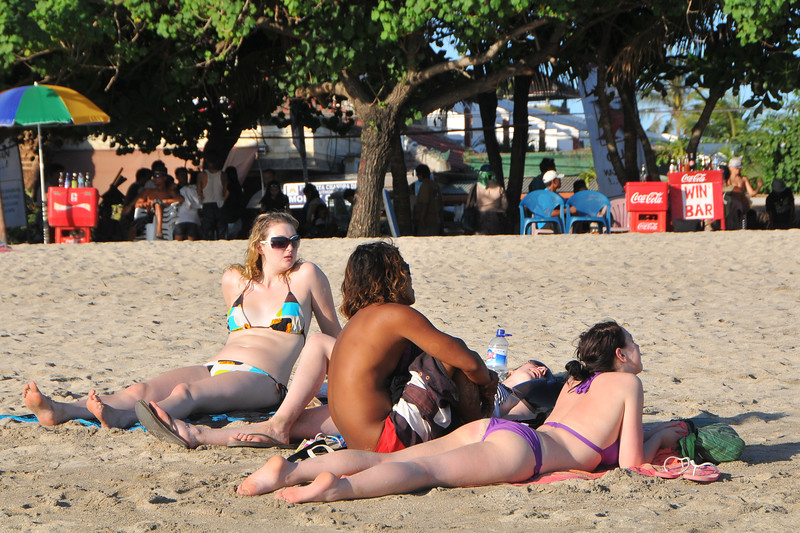 Many Australians come to just chill-out and get a good tan.<br /> <br /> Kuta District (Indonesian: Kecamatan Kuta) is administratively a district (Kecematan) and subdistrict/village (Kelurahan) in southern Bali, Indonesia. Although popularly Kuta is famous for its beach front.<br /> <br /> A former fishing village, it was one of the first towns on Bali to see substantial tourist development, and as a <br /> beach resort remains one of Indonesia's major tourist destinations. It is known internationally for its long <br /> sandy beach, great waters, varied accommodation, many restaurants and bars, and many renowned surfers who visit from Australia. It is located not far from Bali's Ngurah Rai International Airport. With a long, broad beach on the Indian Ocean, Kuta was originally discovered by tourists as a surfing mecca. It has long been a stop on the classic backpacking route in Asia. It can at times be quite chaotic & overcrowded however, the 5 Km long arcing white sand stretch of Kuta is still arguably the best beach front on Bali. The beach is partially clean although the vendors remain annoying and bugging. The long stretch of sand, is full of sunbathers and holiday makers.  Most of the serious surfers have moved on to newer pastures, still one can find that there are tons of surfer around on Kuta beach.