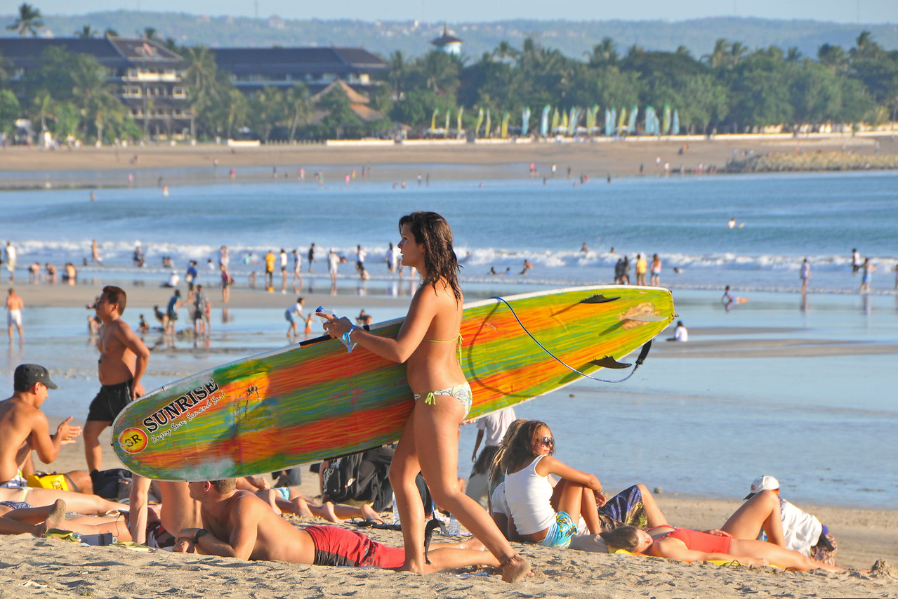 Surfing is still very popular on Kuta Beach.<br /> <br /> Kuta District (Indonesian: Kecamatan Kuta) is administratively a district (Kecematan) and subdistrict/village (Kelurahan) in southern Bali, Indonesia. Although popularly Kuta is famous for its beach front.<br /> <br /> A former fishing village, it was one of the first towns on Bali to see substantial tourist development, and as a <br /> beach resort remains one of Indonesia's major tourist destinations. It is known internationally for its long <br /> sandy beach, great waters, varied accommodation, many restaurants and bars, and many renowned surfers who visit from Australia. It is located not far from Bali's Ngurah Rai International Airport. With a long, broad beach on the Indian Ocean, Kuta was originally discovered by tourists as a surfing mecca. It has long been a stop on the classic backpacking route in Asia. It can at times be quite chaotic & overcrowded however, the 5 Km long arcing white sand stretch of Kuta is still arguably the best beach front on Bali. The beach is partially clean although the vendors remain annoying and bugging. The long stretch of sand, is full of sunbathers and holiday makers.  Most of the serious surfers have moved on to newer pastures, still one can find that there are tons of surfer around on Kuta beach.