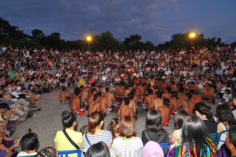 """Kecak Dance (also called """"monkey dance"""") being performaned at Uluwatu.<br /> <br /> This dance is held at the temple daily between 6 pm and 7 pm. This show was invented for and performed for tourists and can be followed up with a dinner.<br /> <br /> Pura Luhur Uluwatu, Bali. <br /> Pura Luhur Uluwatu is one of Bali's kayangan jagat (directional temples) and guards Bali from evil spirits from the south-west. Major Hindu deities dwell in Uluwatu such as - Bhatara Rudra, God of the elements and of cosmic force majeures. Bali's most spectacular temples located high on a cliff top at the edge of a plateau 250 feet above the waves of the Indian Ocean. Uluwatu lies at the southern tip of Bali in Badung Regency. Dedicated to the spirits of the sea, the famous Pura Luhur Uluwatu temple is an architectural wonder in black coral rock, beautifully designed with spectacular views. This is a popular place to enjoy the sunset. Famous not only for its unique position, Uluwatu also boasts one of the oldest temples in Bali, Pura Uluwatu. Most of Bali's regencies have Pura Luhur (literally high temples or ascension temples) which become the focus for massive pilgrimages during three or five day odalan anniversaries. The photogenic Tanah Lot and the Bat Cave temple, Goa Lawah, are also Pura Luhur. Not all Pura Luhur are on the coast, however but all have inspiring locations, overlooking large bodies of water.<br /> <br /> Uluwatu is a small village on the west coast, south of Jimbaran, but for most visitors it refers only to the famous temple of the same name and several kilometers further south at the coast. A taxi from Kuta to Uluwatu takes about 30 minutes up and down winding roads.<br /> <br /> The temple is inhabited by large number of monkeys, who are extremely adept at snatching visitors' belonging, including bags, cameras and eyeglasses. One has to keep a very close grip on all your belongings. Anu carried a stick like some others and I carried my tripod. :)<br /> If you do ha"""