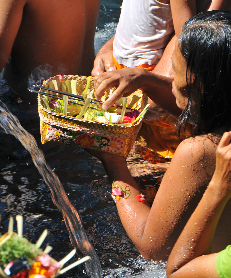 Flowers and other offerings while taking a holy bath at Tirta Empul - The Holy Springs<br /> <br /> Located in Tampak Siring is the Temple Tirta Empul where its pond is believed to cure sickness. Tirta empul means water that comes from the earth naturally. And until this day Balinese still believe the miraculous healing powers of the water and therefore bath in it. According to Usana Bali, an ancient Balinese manuscript, there was once an evil king named Maya Denawa who did not believe in god, and objected to the people worshipping gods. The gods sent a punishment in the form of the warriors of Bhatara Indra, who arrived to attack Maya Denawa and overthrow him. However, Maya Denawa poisoned the warriors and they lay dead. Seeing this, the Hindu God Indra pierced the earth to create a spring called Amerta. When the water was sprinkled over the dead warriors, they became alive again. This water source is believed to be Tirta Empul - the source of life and prosperity to this day. The temple inscriptions mention that Tirta Empul was constructed in 960 AD, when the king Chandrabhaya Singha Warmadewa ordered its construction. During a festival or ceremony you can see many people bathing in the ponds that has seven pancuran. It is believed that the sacred spring water not only can cure sickness but can also purify sins.