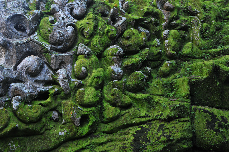 Close up of Goa Gajah.<br /> Elephant Cave, is located on the island of Bali near Ubud and a short distance from Bedulu. Built in the 9th century, it served as a sanctuary. A carved entrance depicts entangling leaves, rocks, animals, ocean waves and demonic human shapes running from the gaping mouth which forms the entrance to the cave. The facade of the cave is a relief of various menacing creatures and demons carved right into the rock at the cave entrance. The primary figure was once thought to be an elephant, hence the nickname Elephant Cave. The site is mentioned in the Javanese poem Desawarnana written in 1365. Inside the cave one finds the Shiva lingum.<br /> <br /> The monstrous Kala head that looms above the entrance seems to part the rock with her hands. Similarly decorated hermit cells are also found in Java. The large earrings indicate that the figure is that of a woman. The T-shaped interior of the rock-hewn cave contained niches which probably served as compartments for ascetics.<br /> <br /> Goa Gajah is named after Sungai Petanu (Elephant River not an elephant as elephants are not found in Bali) and dates back to the 11th Century where it originally served as a dwelling for Hindu priests. Outside the cave at the pavilion is a statue of Men Brayut, the Balinese woman who together with her husband Pan could not stop having kids. The legend of Men Brayut is also represented in local Buddhist writings, under the name of Hariti, indicating a possible Buddhist association with Goa Gajah as well as Hindu.  Outside the cave, an extensive bathing place on the site was not excavated until the 1950s. These appear to have been built to ward off evil spirits. It is an UNESCO World Heritage site.