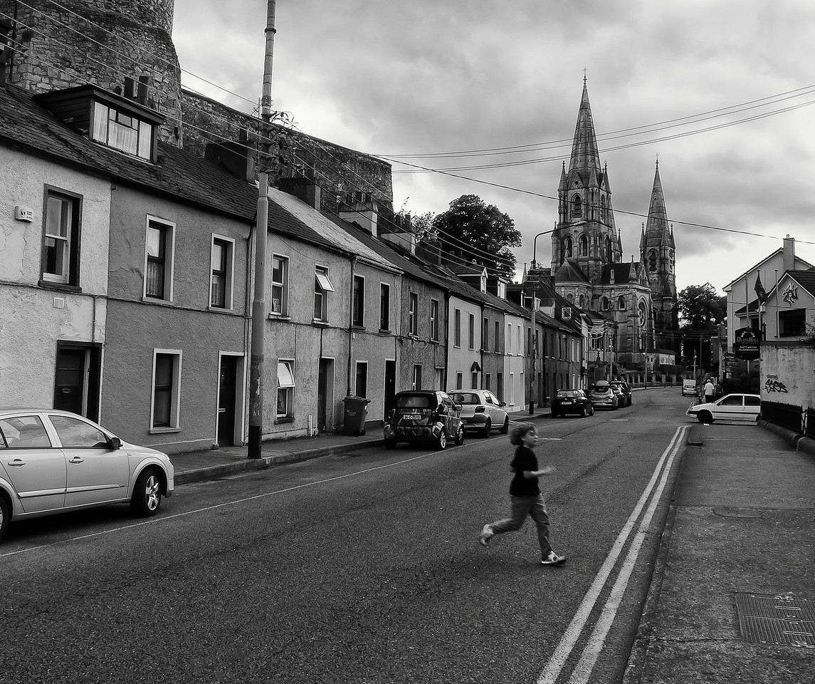 Boy crossing the street in Cork.<br /> <br /> Cork, Ireland, 2013.