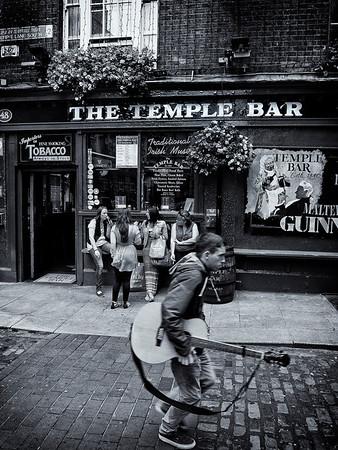 Musician walking past a popular pub in Dublin.  Dublin, Ireland, 2013.