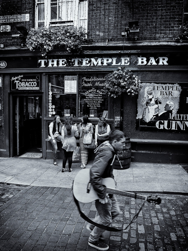 Musician walking past a popular pub in Dublin.<br /> <br /> Dublin, Ireland, 2013.