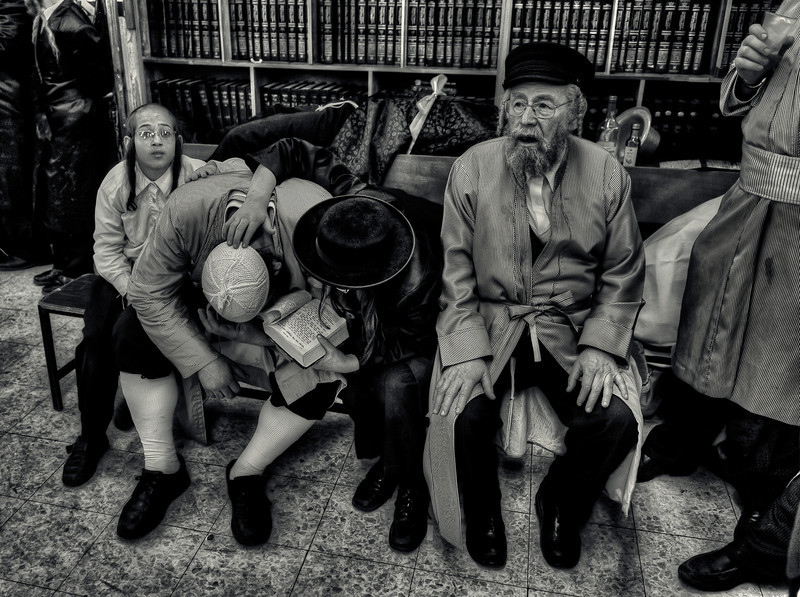 """Son consoles his drunken father with the use of the Torah at a synagogue during the festival of Purim.<br /> <br /> For more on drinking during Purim please visit """"the people of Mea Shaerim"""" under the """"meet the people"""" gallery.<br /> <br /> Mea Shaerim, Jerusalem,Israel, 2012"""