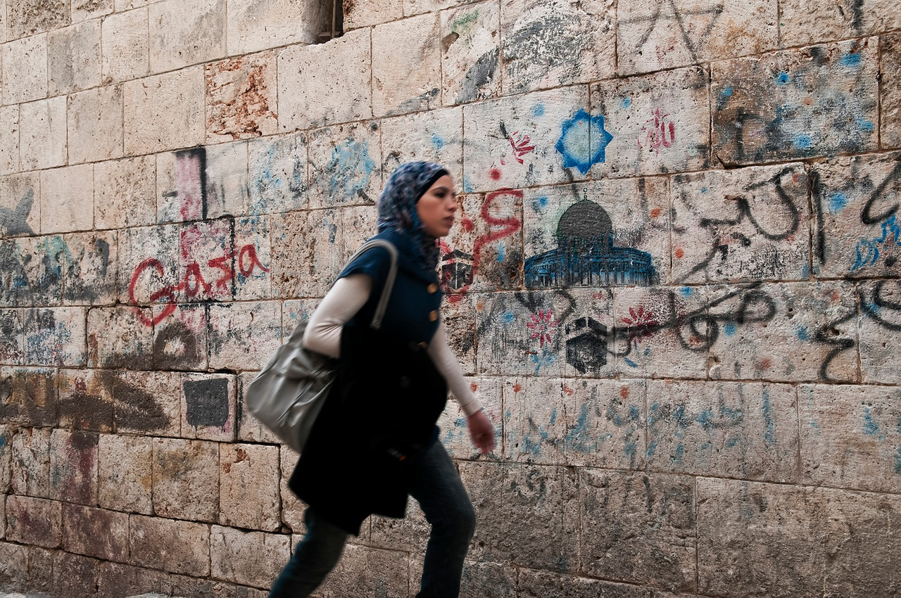 Muslim student walks past the school wall in the Arab Quarter.<br /> <br /> Jerusalem, Israel, 2012.