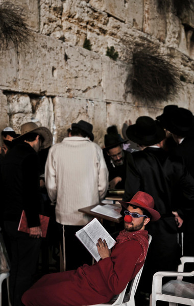 Man dressed in fancy dress during the Purim festival prays at the wailing wall. <br /> <br /> Jerusalem, Israel, 2012.