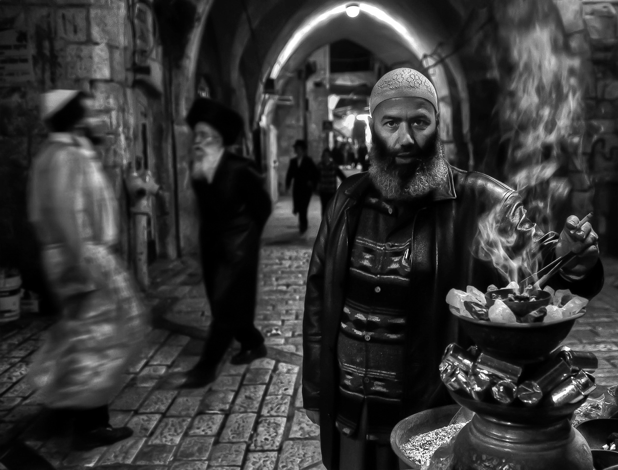 Muslim street vendor with Jewish people seen in the background coming and going from the wailing wall.<br /> <br /> Muslim quarter, Jerusalem, Israel, 2012.