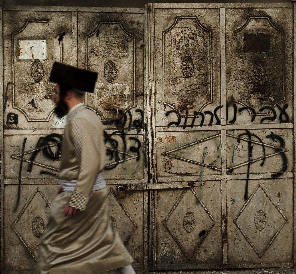 """A Haredim Jew walks past a doorway in the in the ultra-Orthodox neighbourhoodof Mea Shearim, <br /> <br /> For more on Mea Shearim please visit the """"Meet the people"""" gallery.<br /> <br /> Jerusalem, Israel, 2012."""