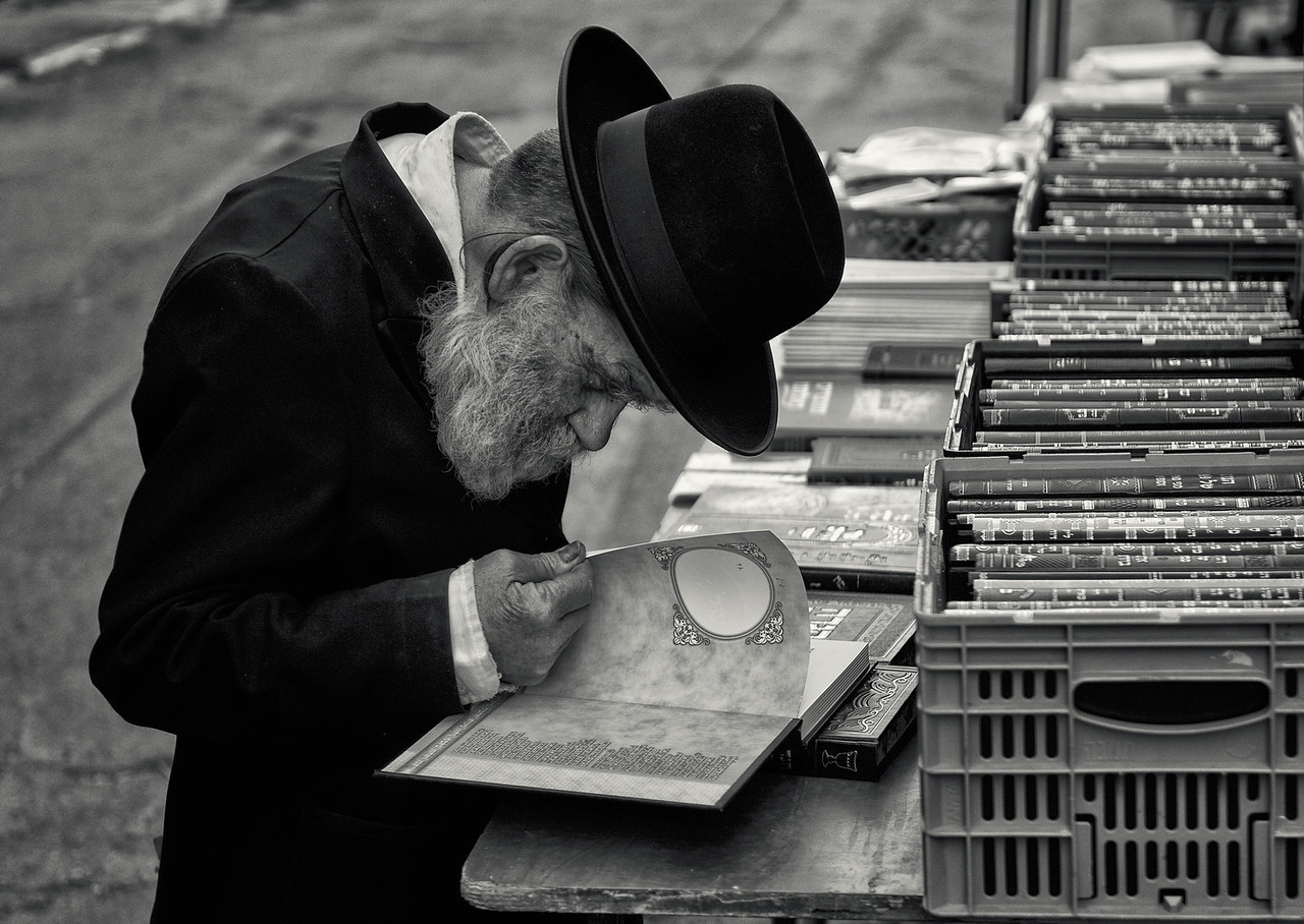"""A Hasidim Jew looks through some holy books at a street stall in the ultra-Orthodox neighbourhood of Mea Shearim, <br /> <br /> For more on the Hasidim please visit """"the people of Mea Shaerim"""" under the """"meet the people"""" gallery.<br /> <br /> Jerusalem,Israel, 2012."""