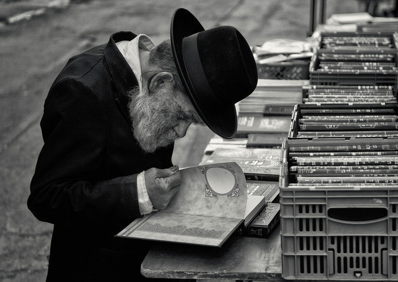 "A Hasidim Jew looks through some holy books at a street stall in the ultra-Orthodox neighbourhood of Mea Shearim, <br /> <br /> For more on the Hasidim please visit ""the people of Mea Shaerim"" under the ""meet the people"" gallery.<br /> <br /> Jerusalem,Israel, 2012."