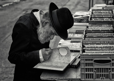 """A Hasidim Jew looks through some holy books at a street stall in the ultra-Orthodox neighbourhood of Mea Shearim,   For more on the Hasidim please visit """"the people of Mea Shaerim"""" under the """"meet the people"""" gallery.  Jerusalem,Israel, 2012."""
