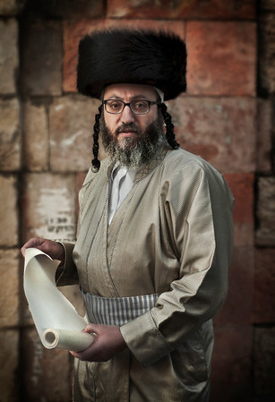 A Haredim holding a copy of a hand written text about Purim.  Mea Shearim, Jerusalem, Israel, 2012.