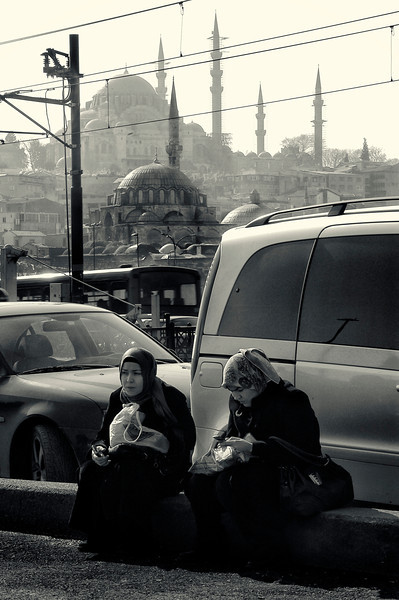 Women having a snack between the busy city traffic.