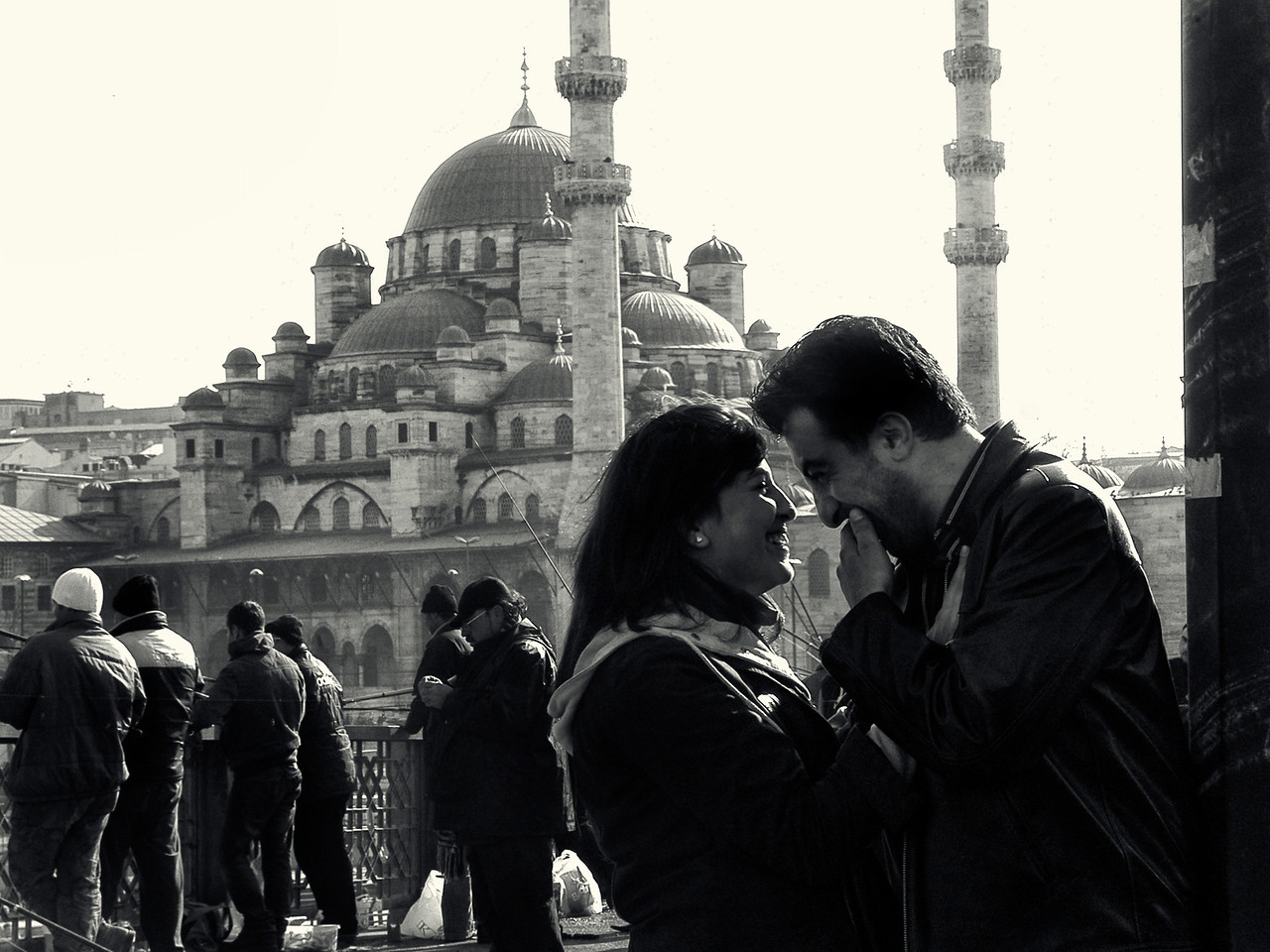 "Only in Istanbul would the construction of the ""New"" Mosque have been finished in 1663 (it was inaugurated in 1665). The mosque is visible from the Galata Bridge were this couple is standing, and is only dwarfed by the Süleymaniye Mosque on the horizon.<br /> <br /> Istanbul, 2009."