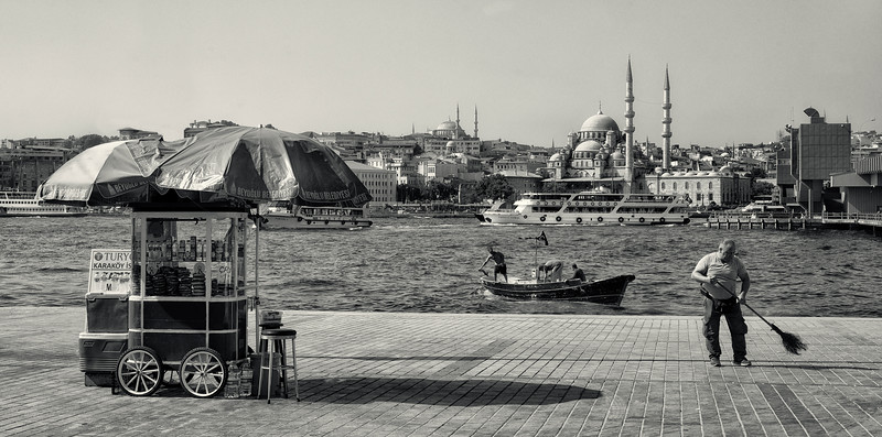 Man cleaning the street around his stall on the shores of the Golden Horn.<br /> <br /> Istanbul, turkey, 2016