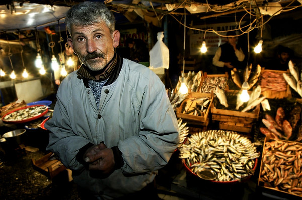 Man selling fish at a small fish market under the Galata Bridge.  Istanbul, 2009.