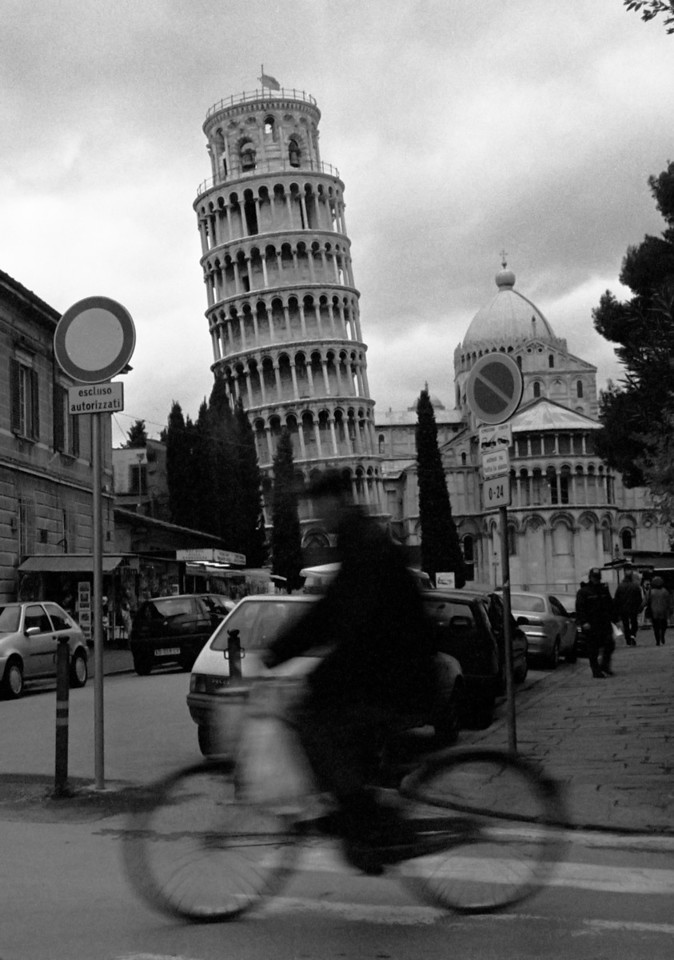 View of the Leaning Tower from a side street.<br /> Construction of the tower occurred in three stages across 177 years. Work on the ground floor of the white marble campanile began on August 8, 1173, during a period of military success and prosperity. This ground floor is a blind arcade articulated by engaged columns with classical Corinthian capitals. <br /> The tower began to sink after construction had progressed to the second floor in 1178. This was due to a mere three-metre foundation, set in weak, unstable subsoil, a design that was flawed from the beginning. Construction was subsequently halted for almost a century, because the Republic of Pisa was almost continually engaged in battles with Genoa, Lucca and Florence. This allowed time for the underlying soil to settle. Otherwise, the tower would almost certainly have toppled. In 1198 clocks were temporarily installed on the third floor of the unfinished construction. <br /> In 1272 construction resumed under Giovanni di Simone, architect of the Camposanto. In an effort to compensate for the tilt, the engineers built upper floors with one side taller than the other. Because of this, the tower is actually curved. Construction was halted again in 1284, when the Pisans were defeated by the Genoans in the Battle of Meloria. <br /> The seventh floor was completed in 1319. It was built by Tommaso di Andrea Pisano, who succeeded in harmonizing the Gothic elements of the bell-chamber with the Romanesque style of the tower. There are seven bells, one for each note of the musical major scale. The largest one was installed in 1655. The bell-chamber was finally added in 1372. <br /> After a phase (1990–2001) of structural strengthening, the tower is currently undergoing gradual surface restoration, in order to repair visual damage, mostly corrosion and blackening. These are particularly pronounced due to the tower's age and its exposure to wind and rain.<br /> <br /> Pisa, Italy.