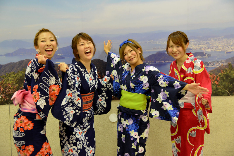 """Japanese ladies in Hiroshima dressed in the kimono (着物?). Kimono is a Japanese traditional garment. The word """"kimono"""", which literally means a """"thing to wear"""" (ki """"wear"""" and mono """"thing""""), has come to denote these full-length robes. Kimono are T-shaped, straight-lined robes worn so that the hem falls to the ankle, with attached collars and long, wide sleeves. Kimono are wrapped around the body, always with the left side over the right (except when dressing the dead for burial.), and secured by a sash called an obi, which is tied at the back. Kimono are generally worn with traditional footwear (especially zōri or geta) and split-toe socks (tabi).<br /> <br /> Hiroshima (広島市) is the capital of Hiroshima Prefecture, and the largest city in the Chūgoku region of western Honshu, which is the largest island of Japan. It is recongnized as the first city in history to be targeted by a nuclear weapon when the United States Army Air Forces (USAAF) dropped an atomic bomb on it at 8:15 a.m. on August 6, 1945, near the end of World War II. Hiroshima is situated on the Ōta River delta, on Hiroshima Bay, facing the Seto Inland Sea on its south side. The river's six channels divide Hiroshima into several islets."""