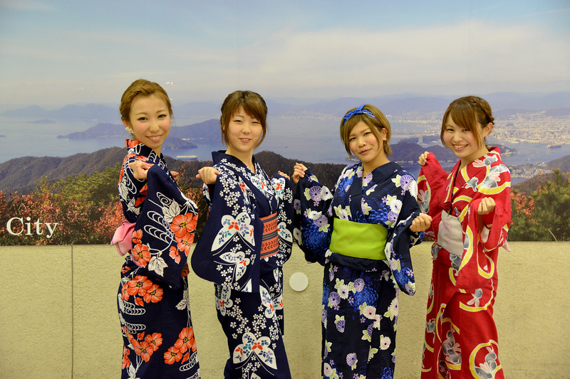 "Japanese ladies in Hiroshima dressed in the kimono (着物?). Kimono is a Japanese traditional garment. The word ""kimono"", which literally means a ""thing to wear"" (ki ""wear"" and mono ""thing""), has come to denote these full-length robes. Kimono are T-shaped, straight-lined robes worn so that the hem falls to the ankle, with attached collars and long, wide sleeves. Kimono are wrapped around the body, always with the left side over the right (except when dressing the dead for burial.), and secured by a sash called an obi, which is tied at the back. Kimono are generally worn with traditional footwear (especially zōri or geta) and split-toe socks (tabi).<br /> <br /> Hiroshima (広島市) is the capital of Hiroshima Prefecture, and the largest city in the Chūgoku region of western Honshu, which is the largest island of Japan. It is recongnized as the first city in history to be targeted by a nuclear weapon when the United States Army Air Forces (USAAF) dropped an atomic bomb on it at 8:15 a.m. on August 6, 1945, near the end of World War II. Hiroshima is situated on the Ōta River delta, on Hiroshima Bay, facing the Seto Inland Sea on its south side. The river's six channels divide Hiroshima into several islets."
