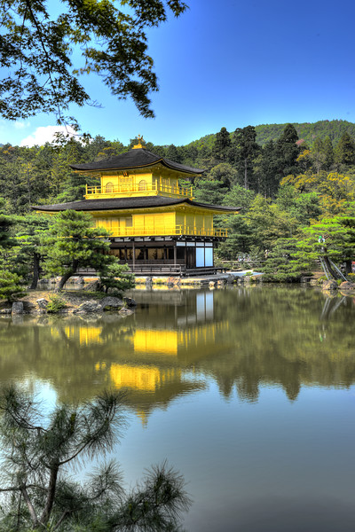 "Kinkaku-ji (金閣寺),""Temple of the Golden Pavilion"" is officially named Rokuon-ji (鹿苑寺)  ""Deer Garden Temple"". It is a Zen Buddhist temple in Kyoto, Japan. The garden complex is an excellent example of Muromachi period garden design. The Muromachi period is considered to be a classical age of Japanese garden design. The correlation between buildings and its settings were greatly emphasized during this period. It was a way to integrate the structure within the landscape in an artistic way. The garden designs were characterized by a reduction in scale, a more central purpose, and a distinct setting. A minimalistic approach was brought to the garden design, by recreating larger landscapes in a smaller scale around a structure.<br /> <br /> Kyoto (京都市) is a city located in the central part of the island of Honshu, Japan. It has a population close to 1.5 million. Formerly the imperial capital of Japan for more than one thousand years, it is now the capital of Kyoto Prefecture, as well as a major part of the Kyoto-Osaka-Kobe metropolitan area. With temples, parks, bustling business districts, markets, from regal estates to the tightly-packed neighborhoods, Kyoto is one of the oldest and most famous Asian metropolises. Although ravaged by wars, fires, and earthquakes during its eleven centuries as the imperial capital, Kyoto was spared from much of the destruction of World War II. With its 2000 religious places- 1600 Buddhist temples and 400 Shinto shrines, as well as palaces, gardens and architecture intact, it is one of the best preserved cities in Japan."