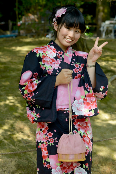 """At Kinkaku-ji (金閣寺),""""Temple of the Golden Pavilion"""", a japanese lady dressed in the kimono (着物?) strikes a pose for the camera. The Kimono is a Japanese traditional garment. The word """"kimono"""", which literally means a """"thing to wear"""" (ki """"wear"""" and mono """"thing""""), has come to denote these full-length robes. Kimono are T-shaped, straight-lined robes worn so that the hem falls to the ankle, with attached collars and long, wide sleeves. Kimono are wrapped around the body, always with the left side over the right (except when dressing the dead for burial.), and secured by a sash called an obi, which is tied at the back. Kimono are generally worn with traditional footwear (especially zōri or geta) and split-toe socks (tabi)."""