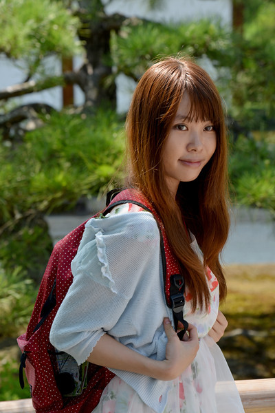 """You lady strikes a pose at Kinkaku-ji (金閣寺),""""Temple of the Golden Pavilion"""". <br /> Kyoto (京都市) is a city located in the central part of the island of Honshu, Japan. It has a population close to 1.5 million. Formerly the imperial capital of Japan for more than one thousand years, it is now the capital of Kyoto Prefecture, as well as a major part of the Kyoto-Osaka-Kobe metropolitan area. With temples, parks, bustling business districts, markets, from regal estates to the tightly-packed neighborhoods, Kyoto is one of the oldest and most famous Asian metropolises. Although ravaged by wars, fires, and earthquakes during its eleven centuries as the imperial capital, Kyoto was spared from much of the destruction of World War II. With its 2000 religious places- 1600 Buddhist temples and 400 Shinto shrines, as well as palaces, gardens and architecture intact, it is one of the best preserved cities in Japan."""