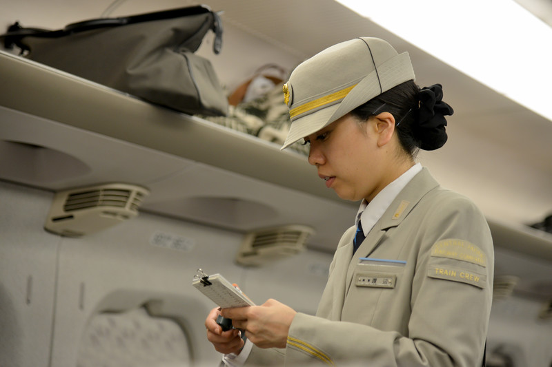 Train ticket checker on the bullet train (Shinkansen (新幹線)) - a network of high-speed railway lines in Japan consist of 2,387.7 km (1,483.6 mi) of lines with maximum speeds of 240–320 km/h (149–199 mph).<br /> <br /> Kyoto (京都市) is a city located in the central part of the island of Honshu, Japan. It has a population close to 1.5 million. Formerly the imperial capital of Japan for more than one thousand years, it is now the capital of Kyoto Prefecture, as well as a major part of the Kyoto-Osaka-Kobe metropolitan area. With temples, parks, bustling business districts, markets, from regal estates to the tightly-packed neighborhoods, Kyoto is one of the oldest and most famous Asian metropolises. Although ravaged by wars, fires, and earthquakes during its eleven centuries as the imperial capital, Kyoto was spared from much of the destruction of World War II. With its 2000 religious places- 1600 Buddhist temples and 400 Shinto shrines, as well as palaces, gardens and architecture intact, it is one of the best preserved cities in Japan.
